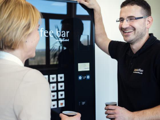 eine Frau und ein Mann stehen lachend vor einem Kaffee- und Heissgetränke Standgerät