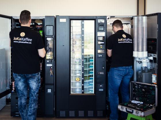 Automatenauffüller und Servicetechniker vor Snackautomat und Kaffee- und Heissgetränke Standgeräten