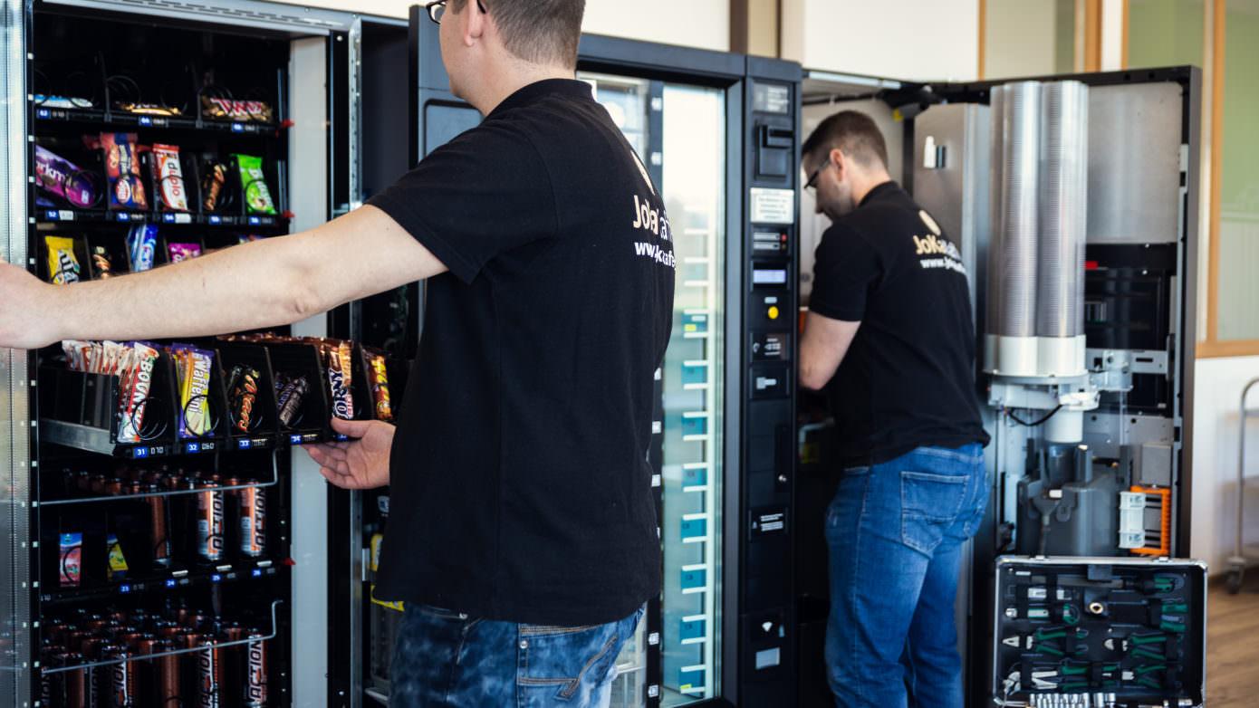 Automatenauffüller und Servicetechniker begutachten Snackautomat und Kaffee- und Heissgetränke Standgeräte
