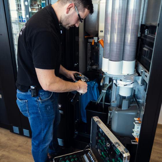 Mann repariert ein Bauteil eines Getränke Standautomaten
