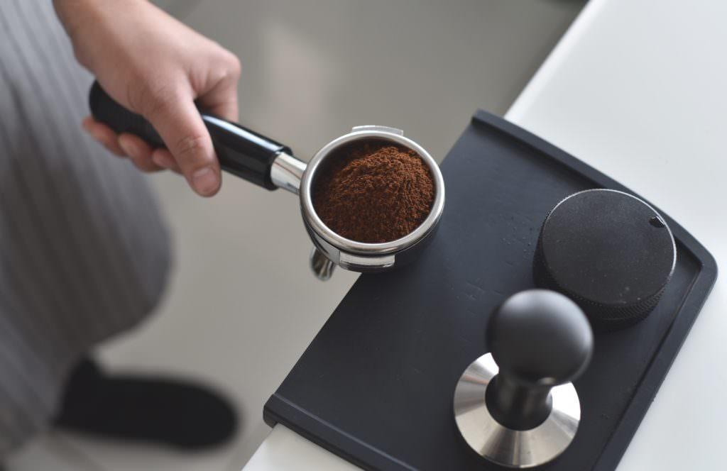 gemahlener Kaffee vor dem Tapern in einem Kaffeesieb