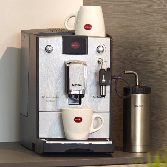 Kaffeevollautomat der Marke Nivona mit Kaffeetassen und einem Milchbehälter
