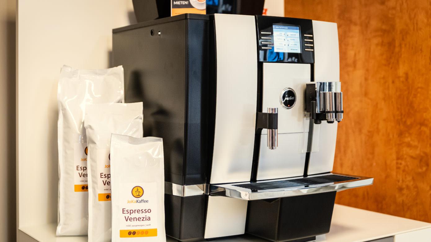 """Jura Kaffeevollautomat auf dem ein Schild steht mit der Beschriftung """"mich kann man mieten!"""". Daneben stehen Verpackungen mit Kaffeebohnen"""