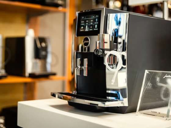 gezeigt wird ein Jura S8 Kaffeevollautomat der chromblitzend vor einem Verkaufsregal steht