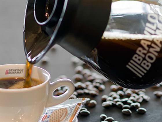 Kaffee wird aus einer Kaffeekanne in eine Kaffeetasse geschüttet